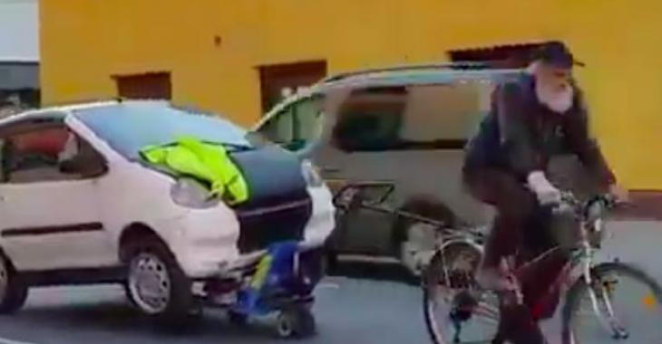 Il remorque une voiture avec son vélo... C'est déconcertant!